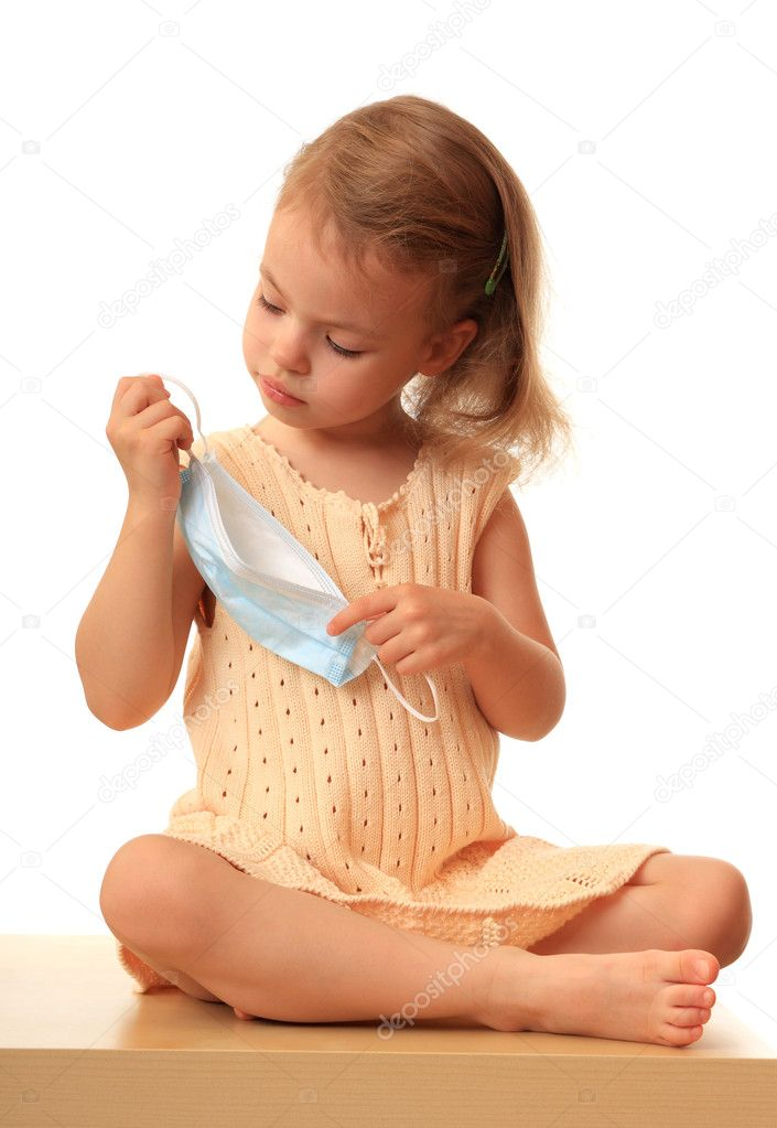 A little girl puts on a non-permanent medical mask.  Stock Photo #1232406