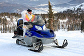 Mountain-skier on a snowmobile. — Stock Photo