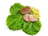 Sliced ham on leaves of salad with a lem — Stock Photo