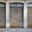 Lowered rolling shutters disused shop — Stock Photo