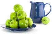 Green apples and blue pitcher — Stock Photo