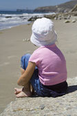 Lonely girl sitting on the beach — Stock Photo