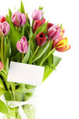 Bouquet of tulips with a blank gift card — Stock Photo