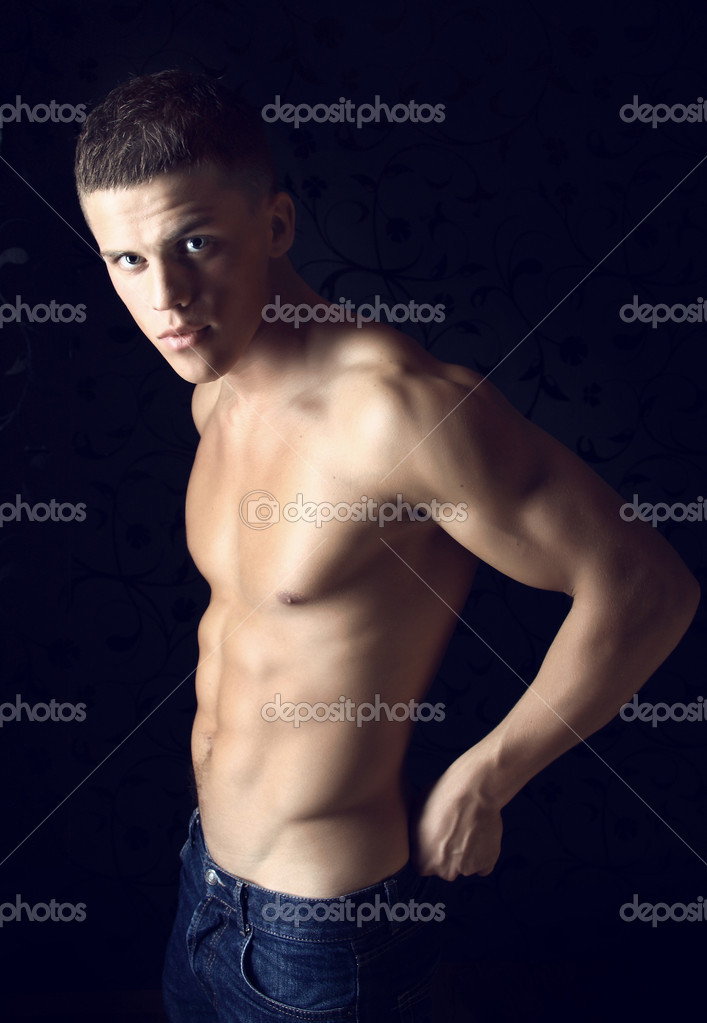Sexual young macho with a beautiful body of the athlete. A photo in a low key.  Stock Photo #1260774