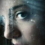 Young girl looking through window — Stock Photo