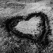 Heart emblem drawn on dried up sand — Stock Photo