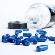 Blue pills spilling out of pill bottle — Stock Photo