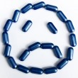 Sad face made by pills - Stock Photo