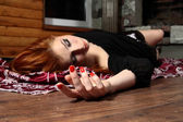 Dead young woman on wooden floor. Studio — Stockfoto