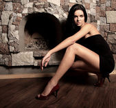 Sexual model near a fireplace — Stock Photo