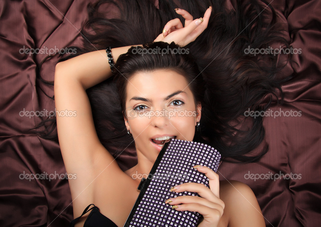 Glamour lady with expensive fashion ladies' handbag laying on brown background. Close-up face photo with copyspace. — Stock Photo #1282631