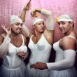 Foto Stock: Three strong men in suits of ballerinas