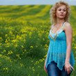 Stock Photo: Young beautiful woman on a green meadow.
