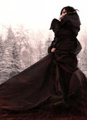 Girl in a long black dress on snow. — Zdjęcie stockowe
