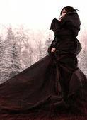 Kar üzerinde uzun siyah elbiseli kız. — Stok fotoğraf