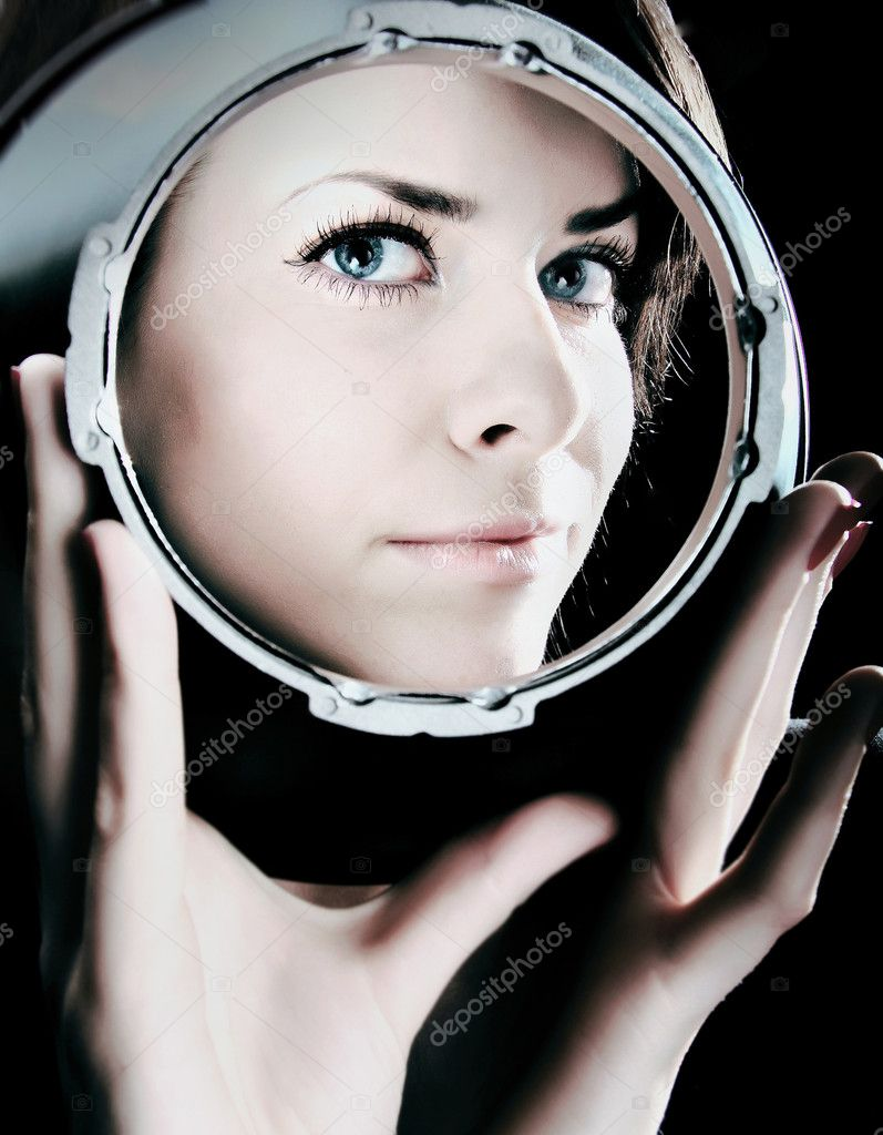 Bewitching portrait of beautiful girl looking through spherical metal capacity. Photo.  Stock Photo #1670525