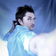 Young attractive macho on blue background — Stock Photo