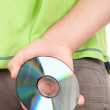 Stock Photo: Hand hides optical disk behind bac