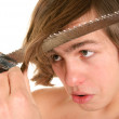 Teenager cuts off saw hair — Stock Photo #2158352