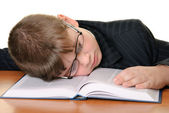 Boy in glasses sleeps on book — Stock Photo