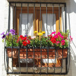 Typical window balcony with flowers in L - Stock Photo