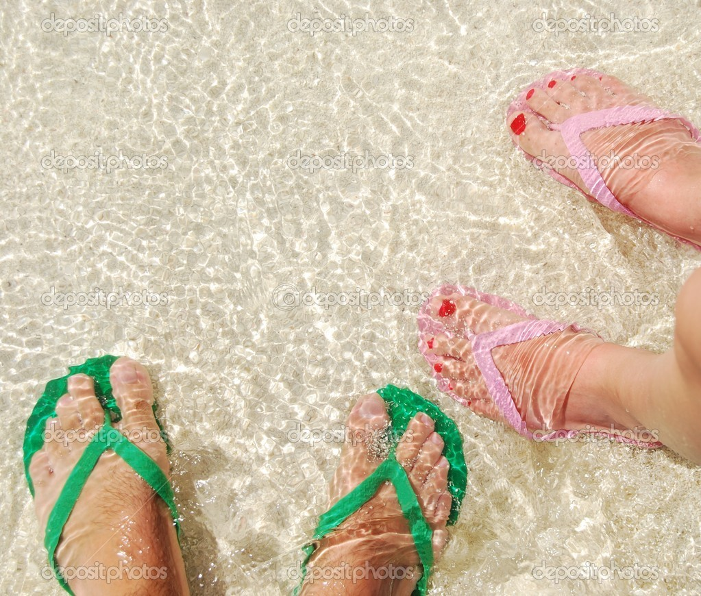 Close up of feet and flip flops on a translucent ocean water — Stock Photo #1299798