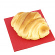 One fresh croissant on a red napkin — Stock Photo