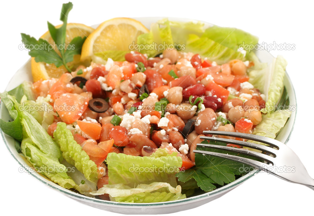 Taking a bit of a fresh and healthy vegetarian bean salad with lettuce and feta cheese on a white background, short depth of field — Stock Photo #1969131