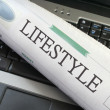 Lifestyle section of newspaper on laptop — Zdjęcie stockowe