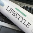 Lifestyle section of newspaper on laptop - Stock Photo