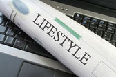 Lifestyle section of newspaper on laptop — Stock Photo