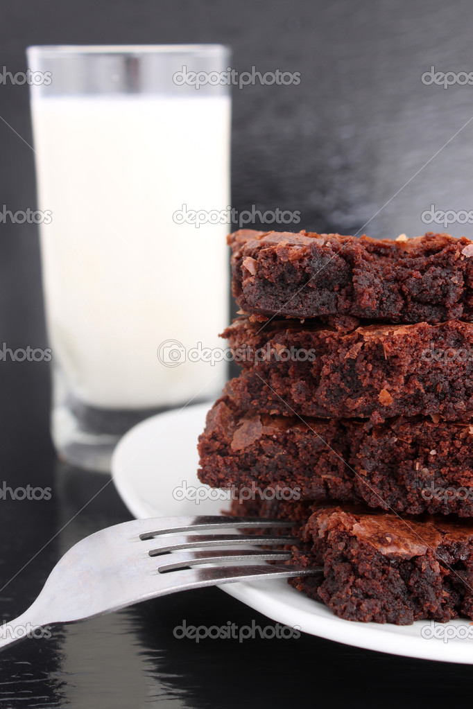 Chocolate fudge brownies on black with glass of milk in the background and a fork on the plate  Stock Photo #1982213