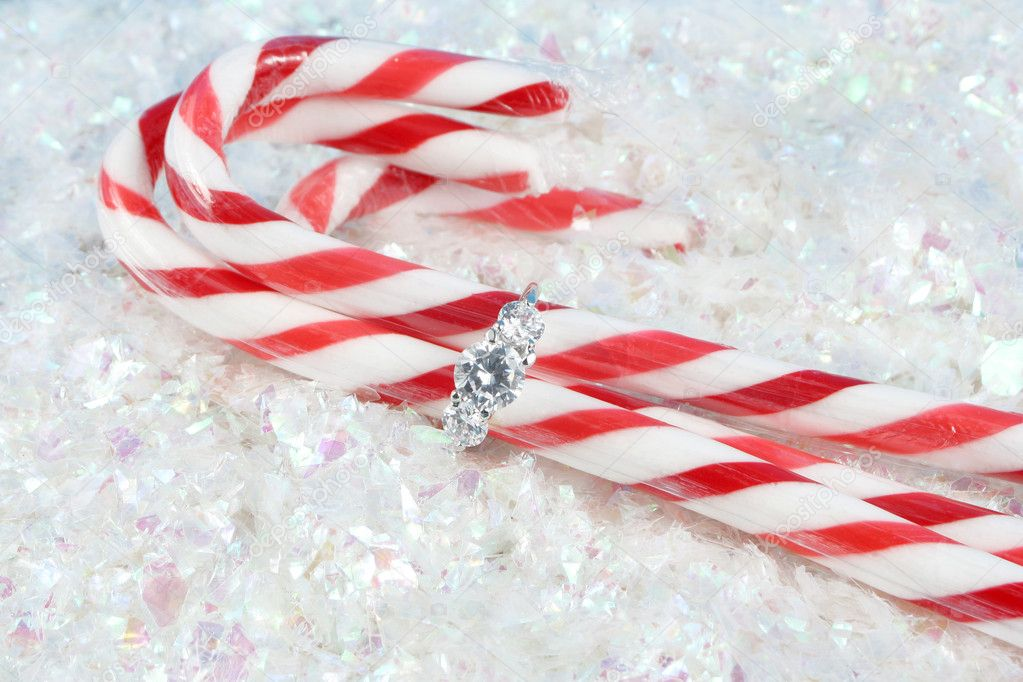 Diamond engagement ring holding candy canes on snowy glitter — Stock Photo #2290453
