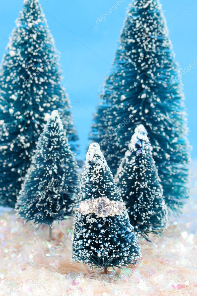 Diamond engagement ring on pine winter tree surrounded by snowy glitter — Stock Photo #2290484