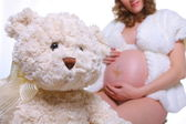 Pregnant woman & teddy bear — Stock Photo