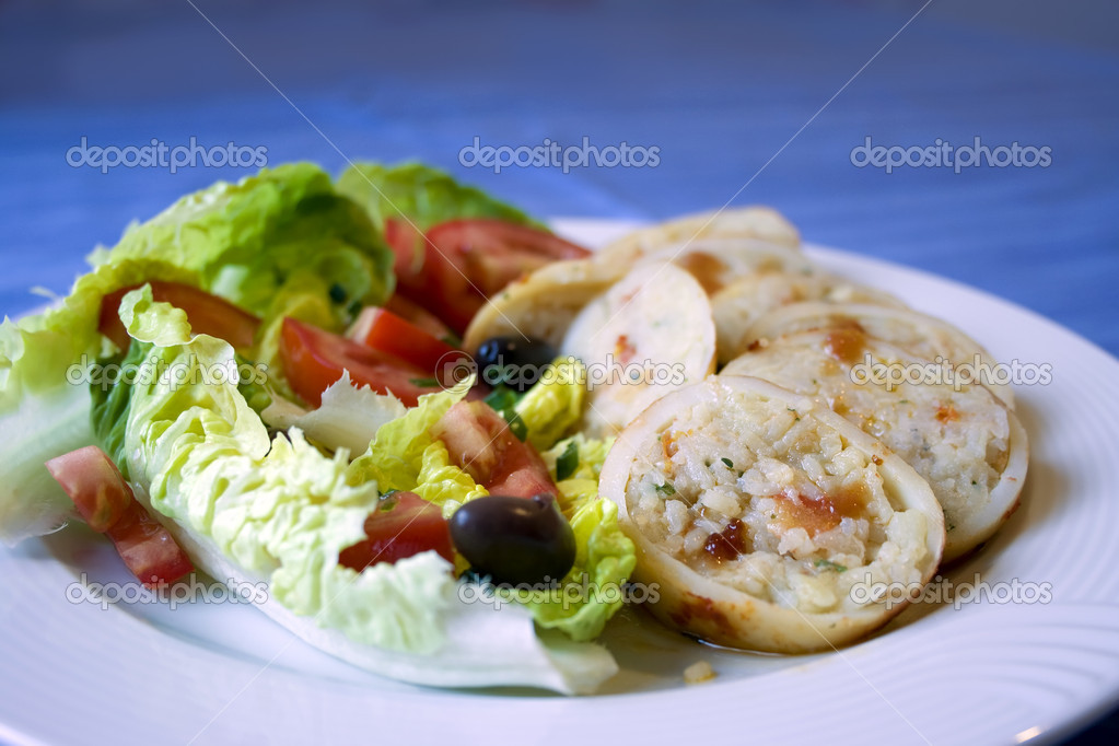 Squid stuffed with rice and greek salad - Stock Image
