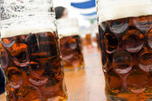 Mugs of dark beer on bavarian festival — Stock Photo