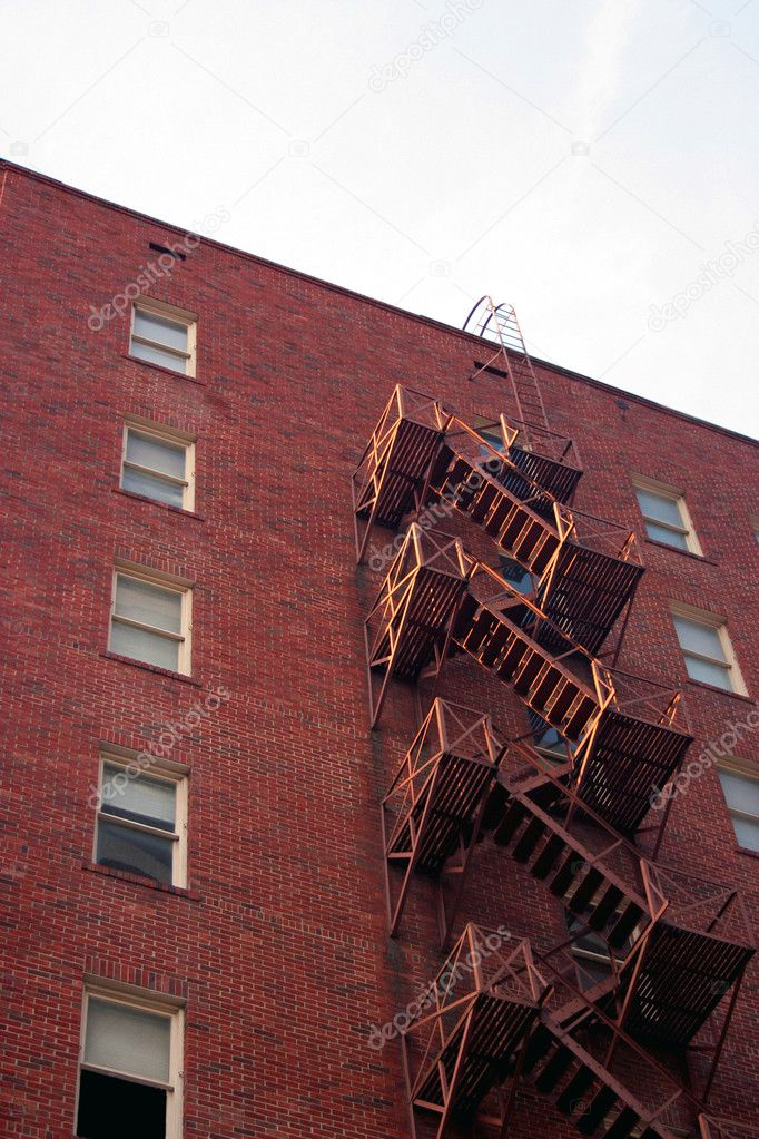 A fire escape going down the side of a brick building — Stock Photo #1331792