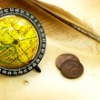 Old globe, feather and  coins — Stock Photo