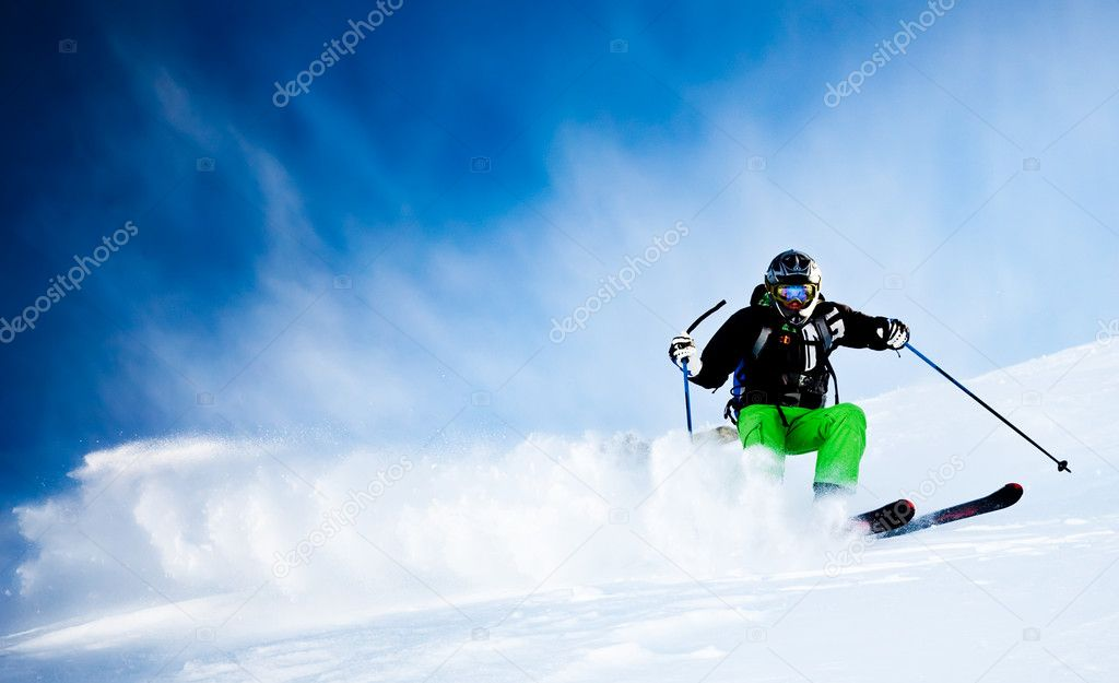 Young male freeride skier over blue sky turning in powder snow; black jacket; green pant; horizontal orientation — Stock Photo #2349257