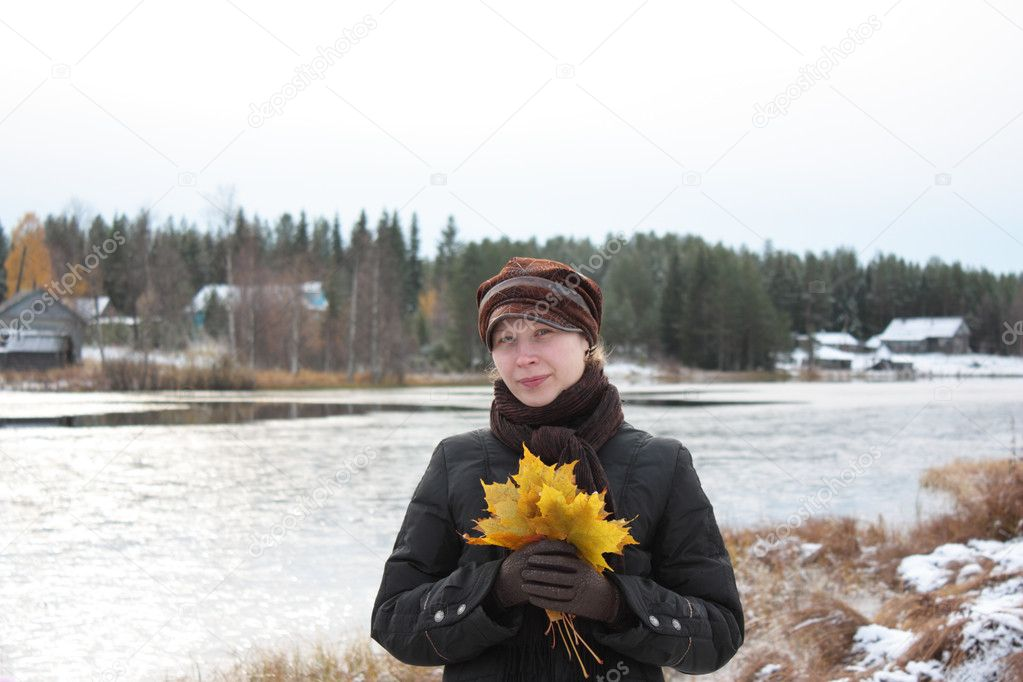 The girl at the lake with a maple leaf.  Stock Photo #1289115