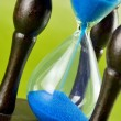 Stock Photo: Hourglass on green