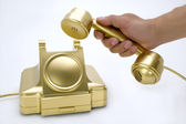 The telephone of gold colour in a hand. — Stock Photo