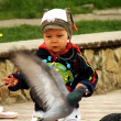 BOY RUNNING AMONG PIGEONS — Stock Photo