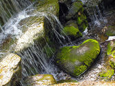 A stone as a heart lies a waterfall — Stock Photo