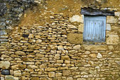 Old yellow stone wall with close window — Stock Photo