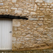 Stock Photo: Old yellow stone wall with white door