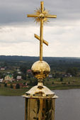 Gold cross with belltower — Stock Photo