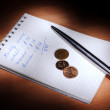 Notebook with pen and coins in the dark — Stock Photo