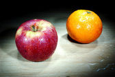 Apple and orange in the dark — Stock Photo
